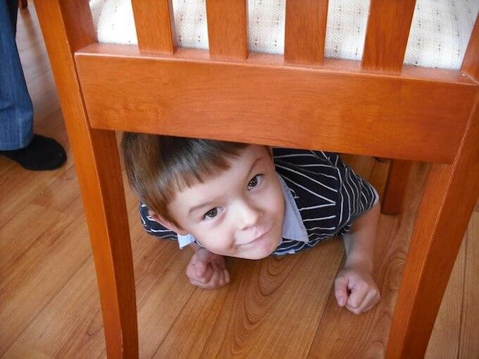 椅子の下から覗いている男の子