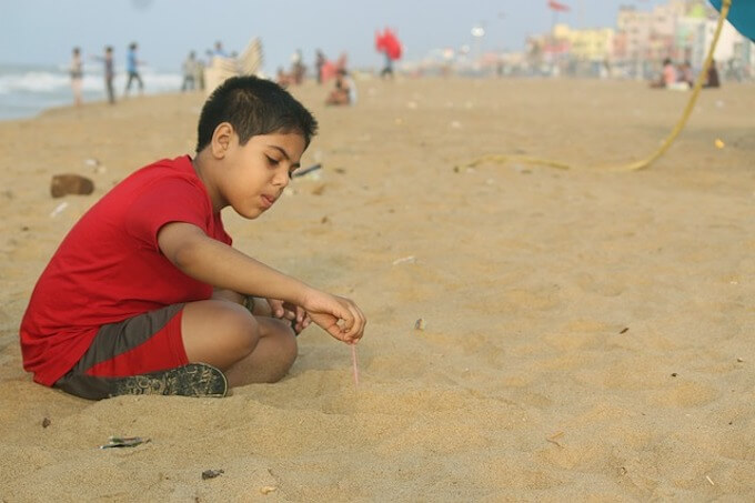 砂浜で遊ぶ少年