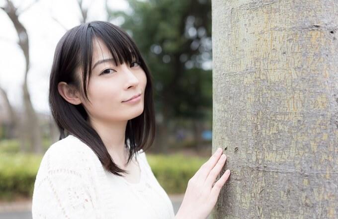 木に寄りかかっている女性