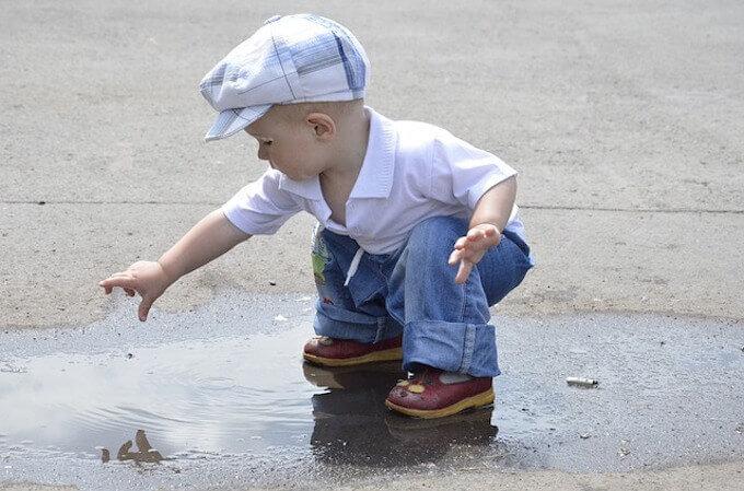 水たまりで遊んでいる子供