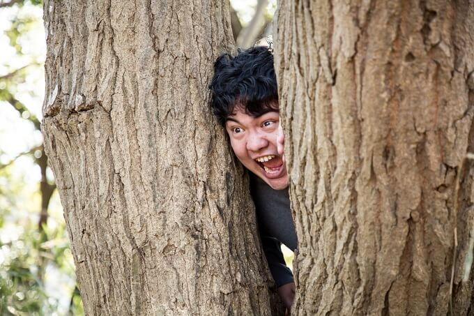 木の間から覗いている男性