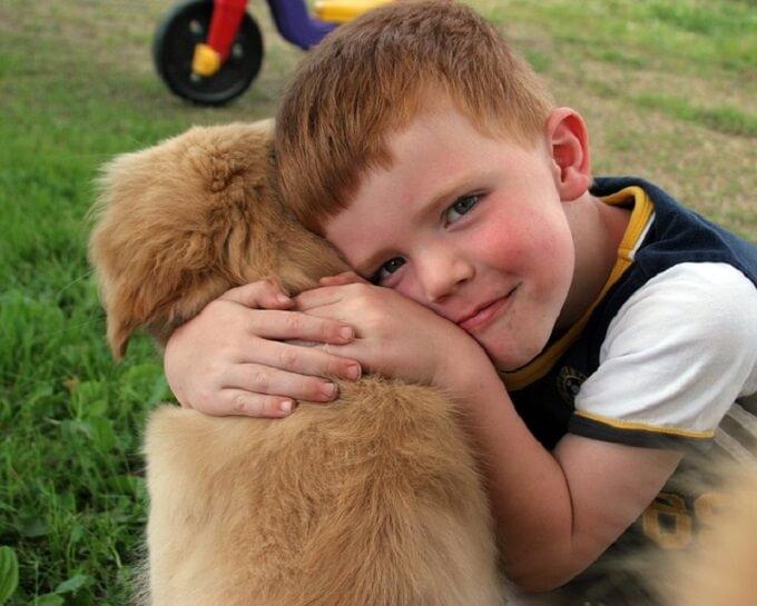 犬を抱いている少年