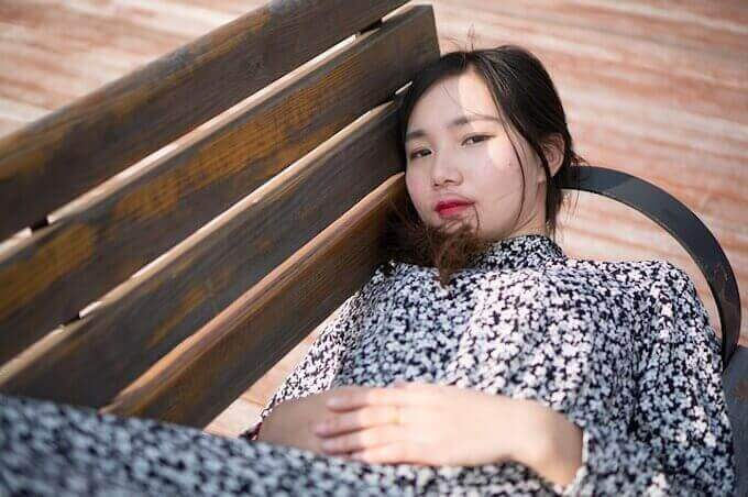ベンチで寝ている女性