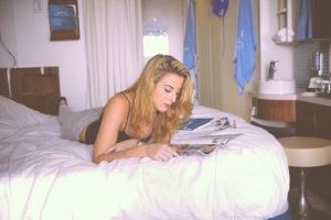 寝ながら読書している女性