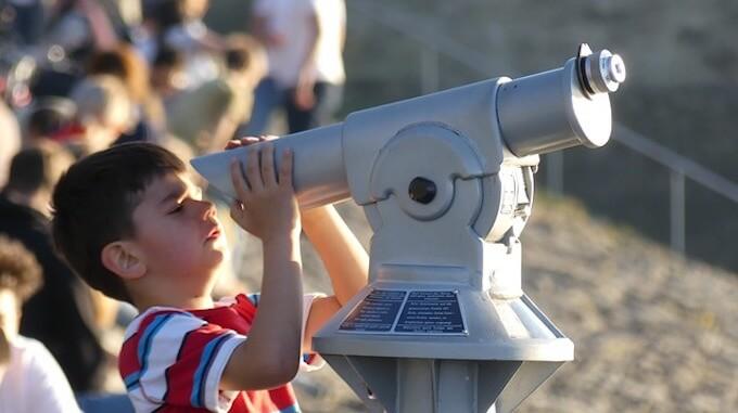 望遠鏡を覗いている少年